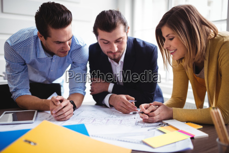 businesswoman with coworkers discussing on blueprint