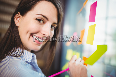 creative businesswoman writing on sticky notes