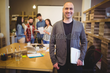 confident businessman standing by table in