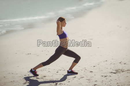 fit woman warming up on beach