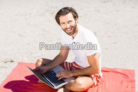man using laptop on beach