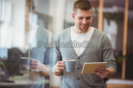 businessman holding coffee cup while using