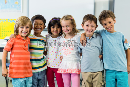 happy schoolchildren standing in classroom