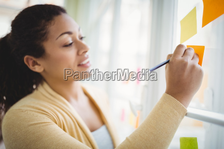 businesswoman writing on adhesive notes in