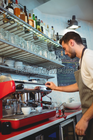 side view of waiter using coffee