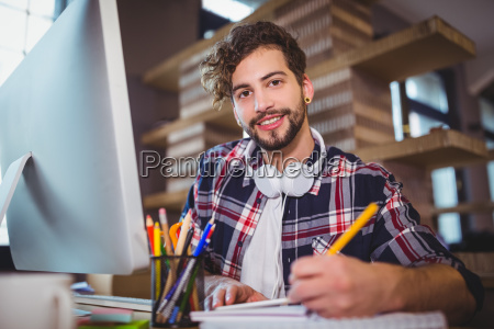 portrait of creative businessman writing in