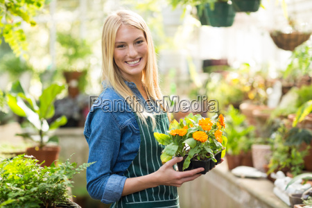 happy beautiful gardener holding potted flowers