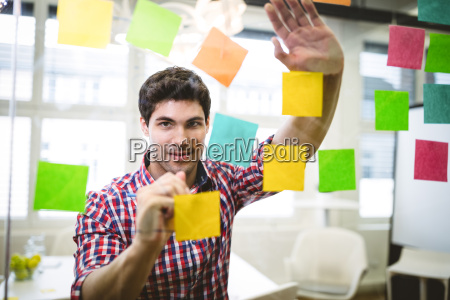 businessman writing on multi colored sticky