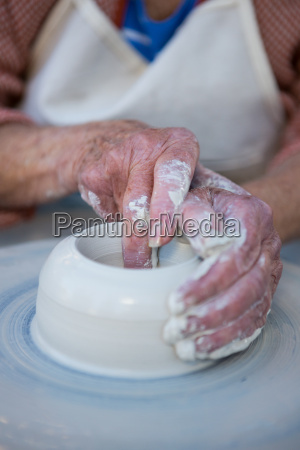 mid section of female potter making