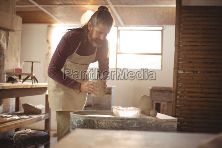 male potter putting clay pottery wheel