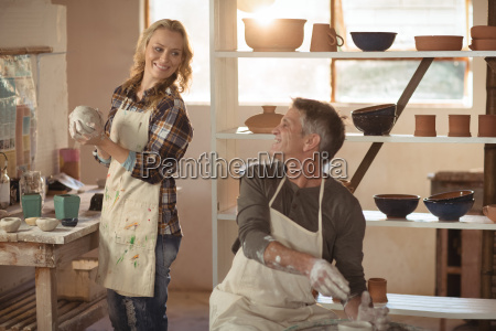 potters interacting while making pot in