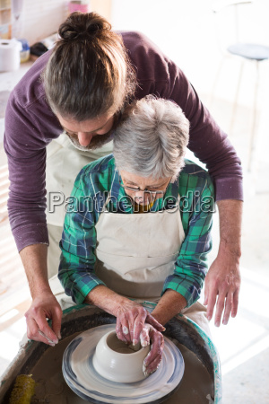 male potter assisting female potter while