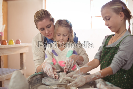 female potter assisting girls