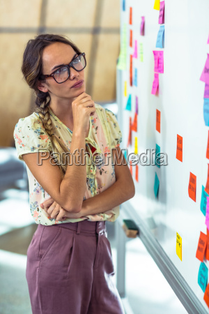 thoughtful woman looking at sticky notes