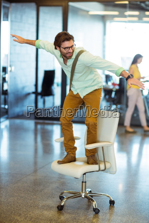 male business executive standing on chair