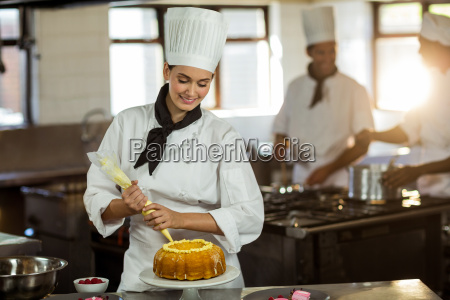 female chef piping icing on cake