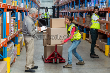 worker is holding heavy cardboard boxes