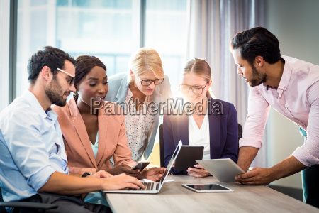 business people interacting using laptop mobile