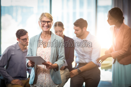businesswoman holding digital tablet while coworker