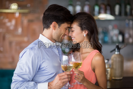 romantic young couple toasting wine glasses
