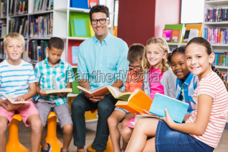 teacher and kids reading book in