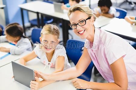schoolgirl and teacher using digital tablet