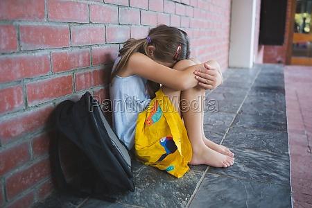 sad schoolkid sitting alone in corridor