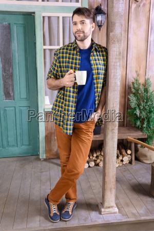 stylish pensive man standing on porch