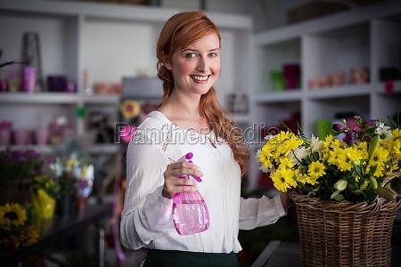 female florist holding spray bottle