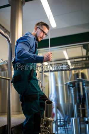 thoughtful brewer holding working equipment