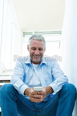 smiling mature man using smartphone at