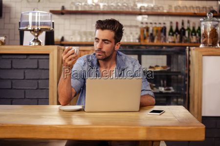 portrait of hipster man sipping coffee