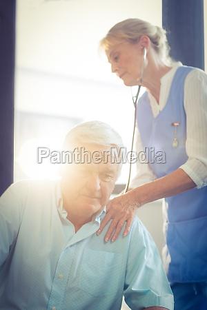 female doctor examining a senior man