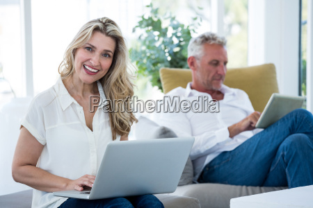 smiling woman with laptop by man