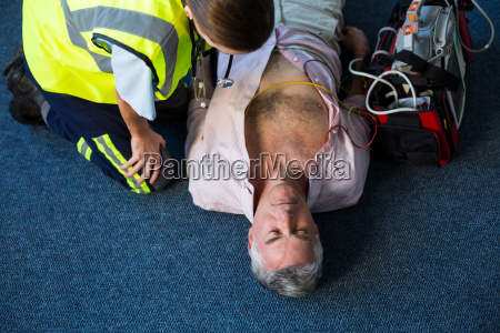 paramedic using an external defibrillator during