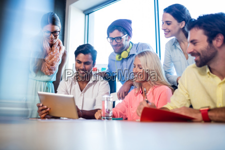 group of coworkers using a tablet