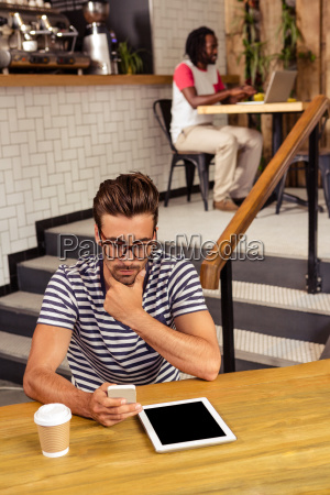 young man sitting at table using