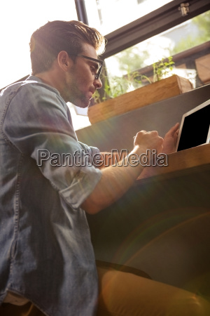 man using a tablet sitting