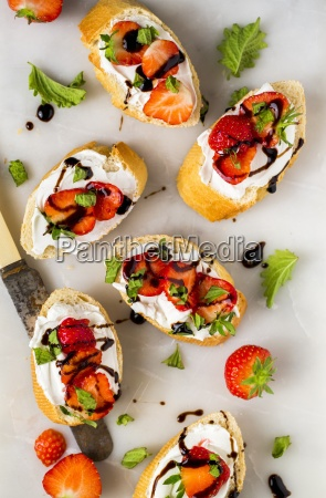 slices of baguette with strawberries basil