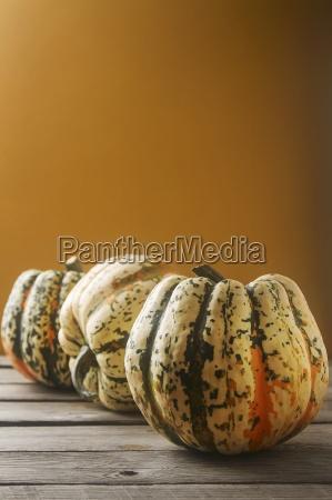 an arrangement of three pumpkins against