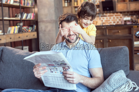 boy closing fathers eyes while reading