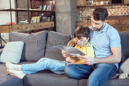 focused father and son reading newspaper