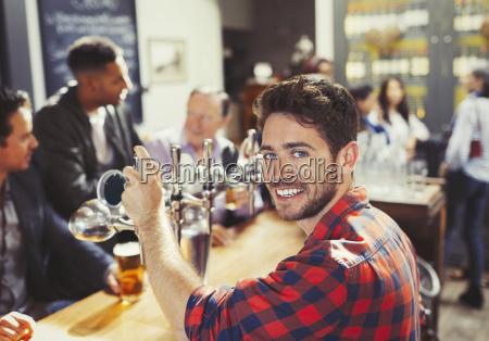 portrait smiling confident male bartender serving