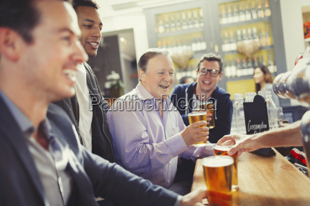 smiling men friends drinking beer at