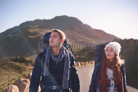young couple with backpacks hiking on