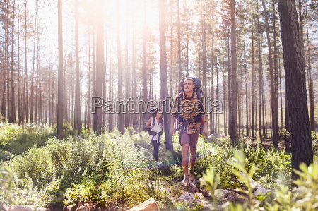 young couple with backpacks hiking in
