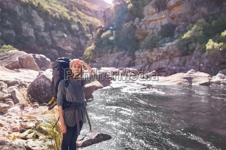 young woman with backpack hiking at