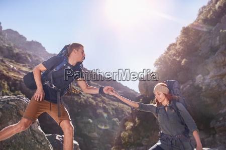 young man helping girlfriend hiking below