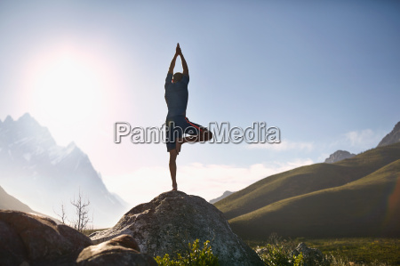 young man balancing in tree pose