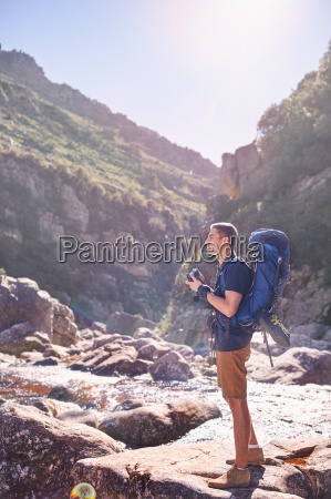 young man with backpack hiking and
